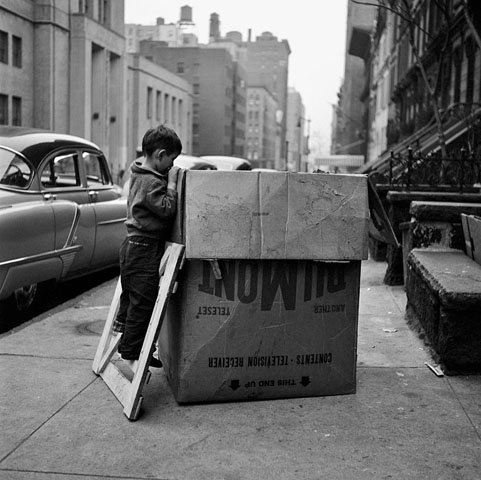 BOY PEERING INTO MOVING BOX, 12 X 12 IN (IMAGE), 20 X 16 IN (PAPER) MODERN GELATIN SILVER PRINT, LTD. ED. OF 15 912