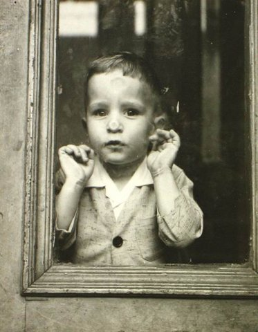 YOUNG BOY LOOKING THROUGH WINDOW C. 1952-1956 4.875 X 3.875 IN (IMAGE) GELATIN SILVER PRINT, ONE OF A KIND