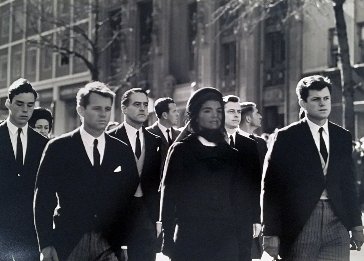 A sorrowing family marches together, JFK Funeral, Washington, DC, 1963
